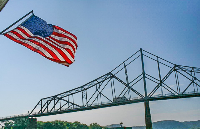 Lansing, Iowa bridge with American flag taken from the back of a yacht